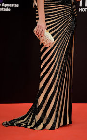 Amaia Salamanca styled her black and nude striped gown with a rhinestone clutch by Oscar de la Renta.