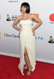 Cardi B looked sleek and elegant in a strapless, double-breasted white gown by Ashi Studio at the Grammy Salute to Industry Icons.