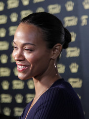 Zoe Saldana styled her hair into a simple twisted bun for the grand opening of Funko Hollywood.