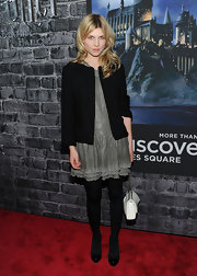 Clemence dons a black tweed jacket over her gray frock at the opening of the Harry Potter exhibit.