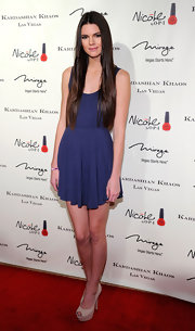 Kendall Jenner wore simple purple cocktail dress with her long locks for the Kardashian Khaos opening.
