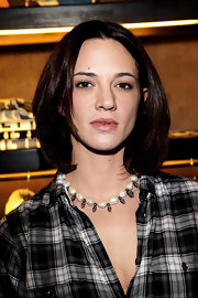 Asia Argento mixed class and edge by wearing a pearl and metal skull bead necklace at a store launch.