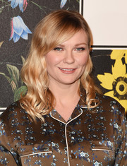 Kirsten Dunst sported a sweet wavy 'do with side-swept bangs at the Erdem x H&M runway show.