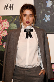Ana de Armas teamed a white ruffle-collar shirt with a gray suit for the Erdem x H&M runway show.