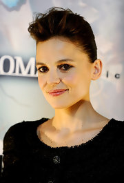 The actress wore a textured volume hairstyle with slicked back sides and a twisted bun.