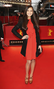 Anelya Adilbekova dressed up her red dress with a fitted black evening coat at the 'Harmony Lessons' premiere in Berlin.