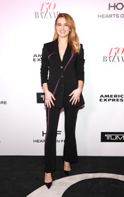 Zoey Deutch kept it low-key in a black Versace pantsuit with purple accents when she attended the Harper's Bazaar 150 Most Fashionable Women celebration.