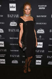 Paris Hilton hit the Harper's Bazaar Icons event wearing a black lace-up off-the-shoulder dress by Moschino.