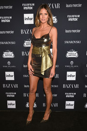 Heidi Klum looked radiant at the Harper's Bazaar Icons event in a gold Redemption mini dress with a complementary oversized belt.