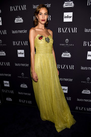 Alexa Chung opted for a whimsical yellow Gucci gown, featuring a ruched bodice, spaghetti straps, and a ladybug embellishment, for her Harper's Bazaar Icons look.