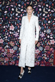 Gigi Hadid looked opulent in a white brocade coat by Chanel Couture at the Harper's Bazaar exhibition.