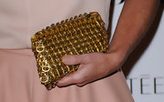 Mariella Frostup showed off a gilded zip around clutch, while walking the red carpet at the Harper's Bazaar Awards.