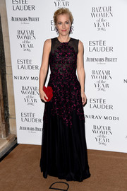 Gillian Anderson added a bright pop with a red velvet clutch by Jimmy Choo.