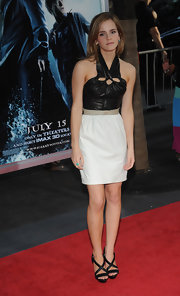 Emma wears black strappy sandals to match her leather top.
