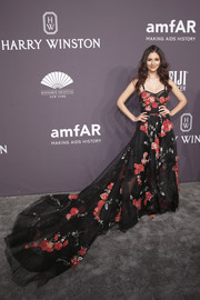 Victoria Justice captivated at the amfAR New York Gala in a black Marchesa gown with red floral appliques and an ultra-long train that the actress paired with  Schutz shoes.