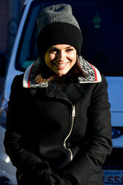 Mila Kunis kept warm with a two-tone beanie and a wool jacket while attending the Hasty Pudding Theatricals parade.