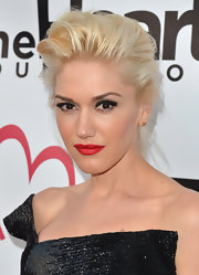 Gwen paired bold smoky eyes and false lashes with brilliant red lipstick.