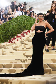 Kylie Jenner put on a curvy display in a strapless black cutout gown by Alexander Wang at the 2018 Met Gala.
