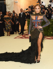 Jennifer Lopez rocked a custom Balmain gown with a cross-beaded bodice, yoke cutouts, and a feathered skirt at the 2018 Met Gala.
