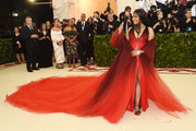 Nicki Minaj made a dramatic entrance in a sweeping red ombre coat by Oscar de la Renta at the 2018 Met Gala.