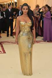 Kim Kardashian flaunted her curves in a gold chainmail gown by Versace at the 2018 Met Gala.