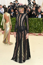 Cara Delevingne went racy in a black fishnet gown by Dior Couture at the 2018 Met Gala.