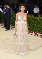 Selena Gomez went for boudoir glamour in a white empire-waist slip gown by Coach at the 2018 Met Gala.