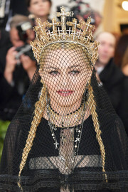 Madonna accessorized with a cross-adorned crown by Rinaldy Yunardi at the 2018 Met Gala.