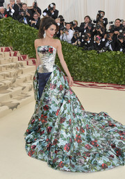 Amal Clooney made a grand entrance in a silver Richard Quinn corset top with a flowing floral train, which she teamed with navy satin trousers, at the 2018 Met Gala.