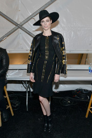 Coco Rocha donned an elegant black bandage dress with gold trim, which she styled with an embellished leather jacket and a hat, for the Herve Leger fashion show.
