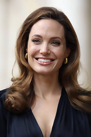 Angelina Jolie wore her lengthy locks with a subtle side part and soft curls while attending a foreign office briefing in London.