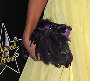 Victoria Hervey wore a decadent purple feathered clutch with her mellow yellow dress.