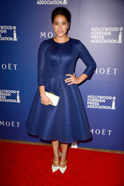 Gina Rodriguez accessorized her outfit with a simple yet elegant white snakeskin clutch by Kotur.