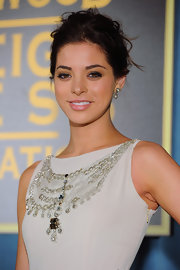 Gia Mantegna highlighted her embellished neckline with a loose updo that exuded elegance.