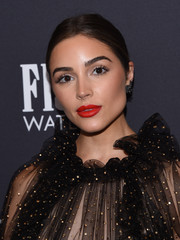 Olivia Culpo attended the Golden Globes 75th anniversary celebration wearing her hair in a classic center-parted bun.