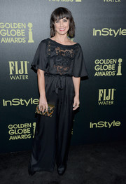 Constance Zimmer wore a black floor-length dress with draped sleeved and a lace detailed bodice.