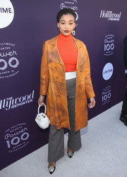 Amandla Stenberg attended the Hollywood Reporter's 2017 Women in Entertainment Breakfast wearing a camel-colored leather coat over a red top and gray pants.
