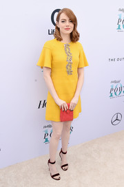 Emma Stone rounded out her colorful ensemble with a red envelope clutch by Tyler Ellis.