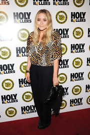 "Mary-Kate Olsen showed off her corky style while hitting the premiere of ""High Rollers"". She paired her fringed clutch with a leopard print blouse."