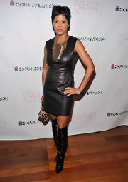 Tamron is fearless in a black leather mini dress with knee boots and a statement necklace.