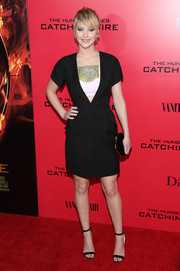 Jennifer Lawrence layered a black wool coat by Dior over an embellished bra top for her red carpet look during the 'Catching Fire' NYC premiere.