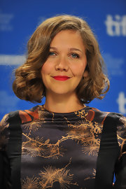To recreate Maggie Gyllenhaal's sweet, retro style, set dry, mid-length hair in hot rollers. To relax the curls slightly, brush tresses with a natural bristle brush, then make a deep side part. Smooth the hair on the top of the head, tousle ends lightly and spritz with a medium-hold hairspray.