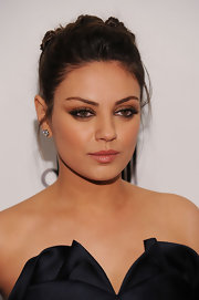 Mila Kunis paired her twisted bun with a soft smoky eye compete with shimmering nude lips.