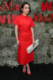 Zoe Lister Jones punctuated her red look with an extra-long white clutch.