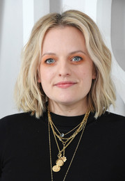 Elisabeth Moss jazzed up her black outfit with layers of gold necklaces.
