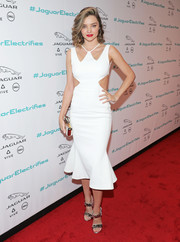 Miranda Kerr flaunted her supermodel figure in a white David Koma dress with waist cutouts and a flared hem during the Jaguar Concept reveal.