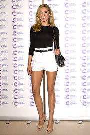 Kimberley Garner chose a black fitted blouse to pair with high-waisted shorts for her relaxed evening look.