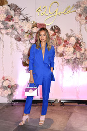Jamie Chung sealed off her vibrant ensemble with a tricolor leather purse by Danse Lente.