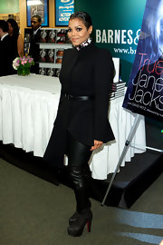 Janet wears a unique asymmetrical black coat with leather pants and boots to her book signing.