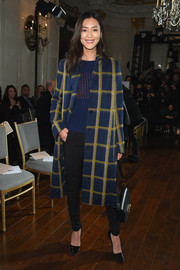 Underneath her coat, Liu Wen wore black skinny pants and a blue and orange sweater.
